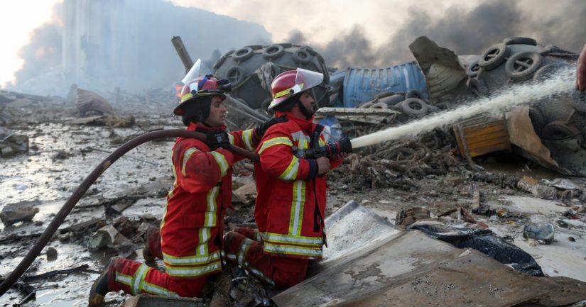 Palomiehet sammuttavat Beirutin satamassa tapahtuneen räjähdyksen aiheuttamia raunioita.