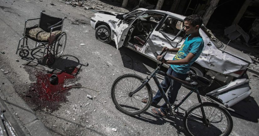 Nuori syyrialaispoika katselee pommitusten jälkiä.