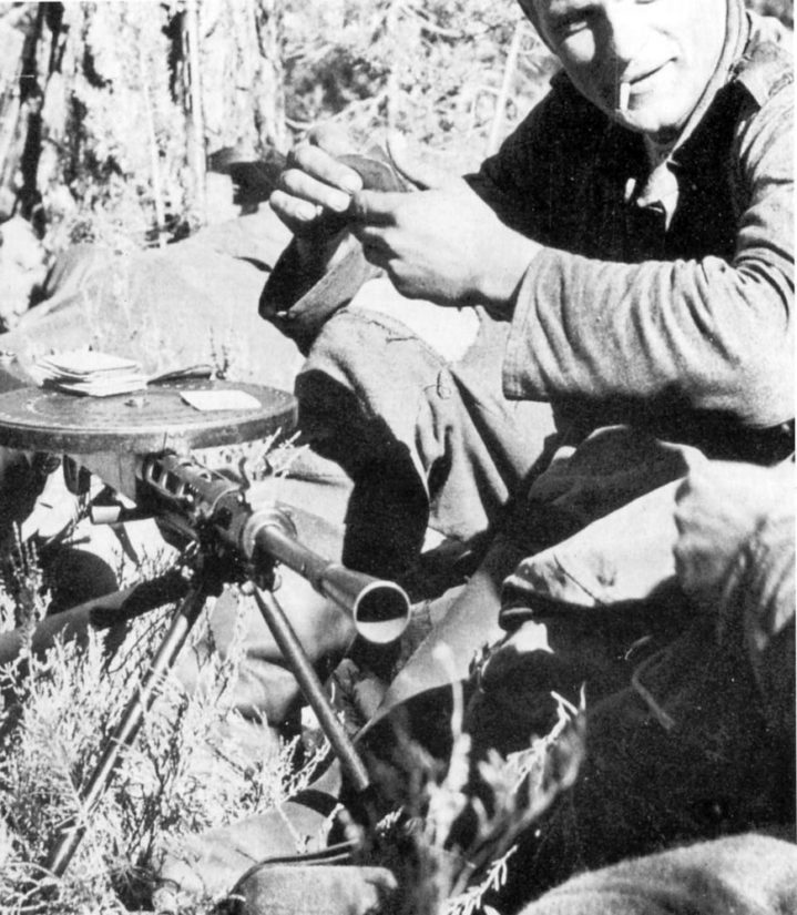 Erkki Lamminen pelaakorttia Mauno Koiviston Emma-pikakiväärin päällä. Ase löytyy nykyisin Sotamuseosta.