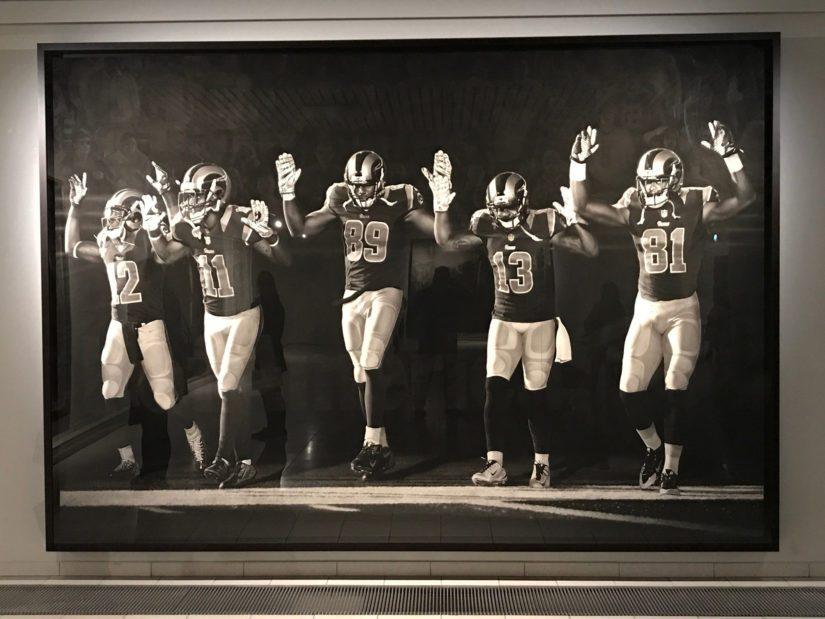 St. Louis Ramsin amerikkalaisen jalkapallon pelaajat nostavat kätensä Longon teoksessa Hands Up.
