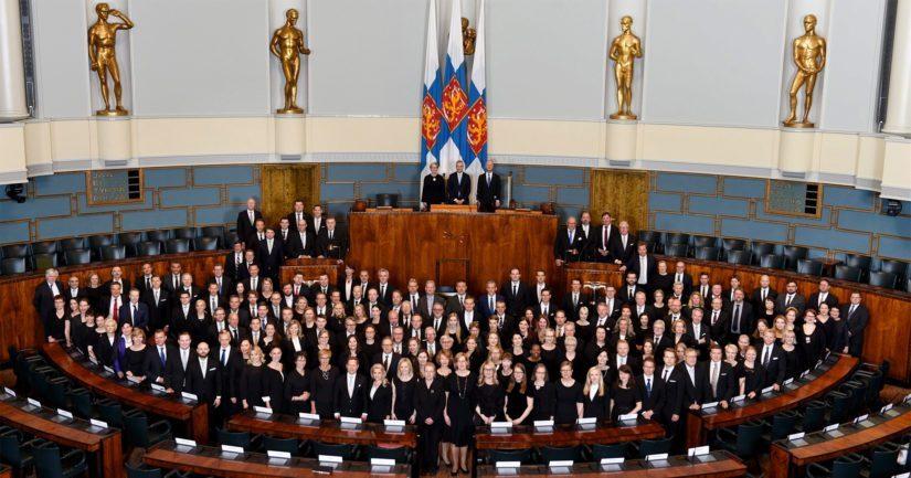 Kansanedustajat ryhmäkuvassa Eduskuntatalon täysistuntosalissa ennen valtiopäivien avajaisia.