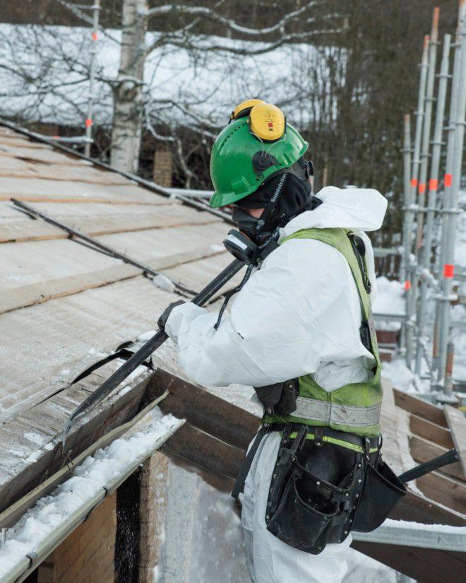 Hämeen Laaturemontin asentaja vanhan katon purkutyössä. Taloa kiertävien telineiden käyttö tarjoaa monta parannusta kattoremonttialan nykyiseen toimintamalliin, jossa asentajat ovat katolla suojakaiteiden ja valjaiden varassa.