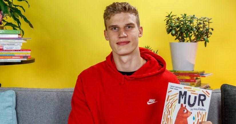 """NBA-koripalloammattilainen Lauri Markkanen lukee kirjan """"Mur ja mustikka""""."""