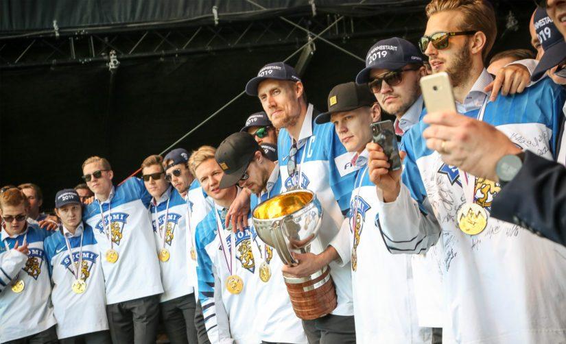 Leijonat kuuntelevat presidentin puhetta, mestaruuspokaali kapteeni Marko Anttilan hallussa.