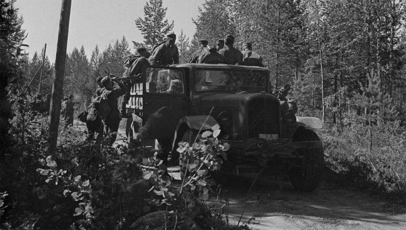 Jääkärikomppania nousee autoihin, jotka vievät sen nopeasti vastaiskupaikan läheisyyteen Tolvajärvellä. Mauno Koiviston hahmon tunnistaa lavalla.
