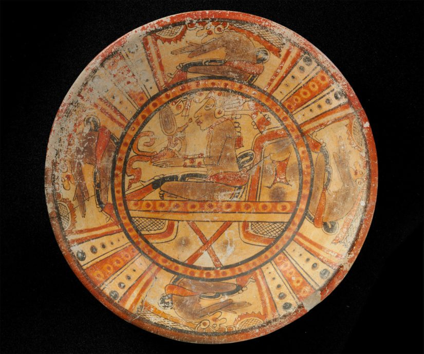 Monivärinen kolmijalkainen lautanen, jossa neljä Pawahtun-jumalaa istuvan nuoren ylimyksen ympärillä. Mayakulttuuri, Guatemala. Klassisen kauden myöhäisvaihe, 600–800 jaa. Keramiikka.