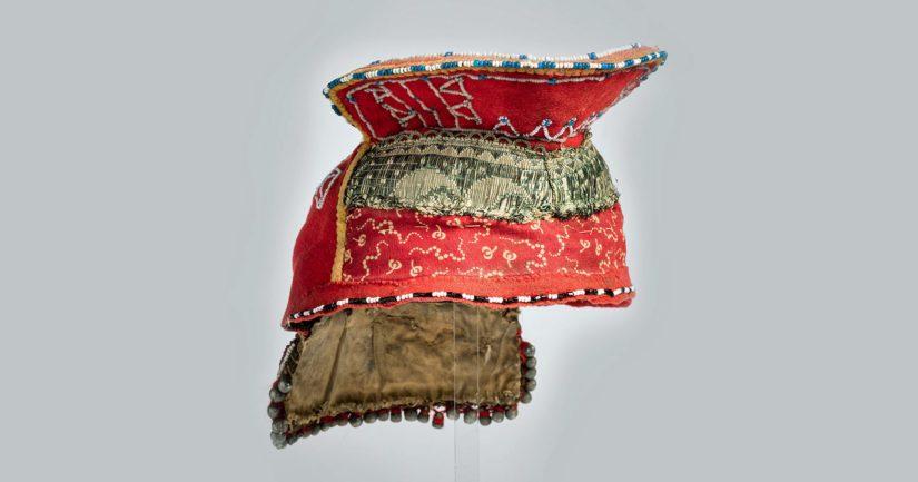 Kolttasaamelainen vaimon päähine kuuluu T.I. Itkosen vuonna 1912 Petsamon Suonikylältä keräämiin esineisiin. Itkoselle sen lahjoitti Kiurel Moshnikov.