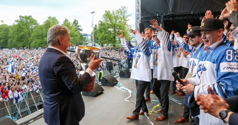 Presidentti Niinistö nostaa Leijonien mestaruuspokaalia kultajuhlissa Kaisaniemessä.