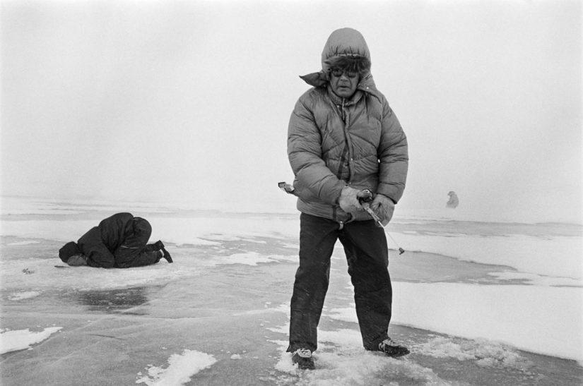 Kekkonen pilkillä Somaslompolossa Käsivarren Lapissa 19.4.1970, rajamies tähystää jään läpi saalista.