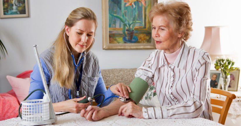 Lähihoitaja kotihoidon työtehtävissään, meneillään verenpaineen mittaus.